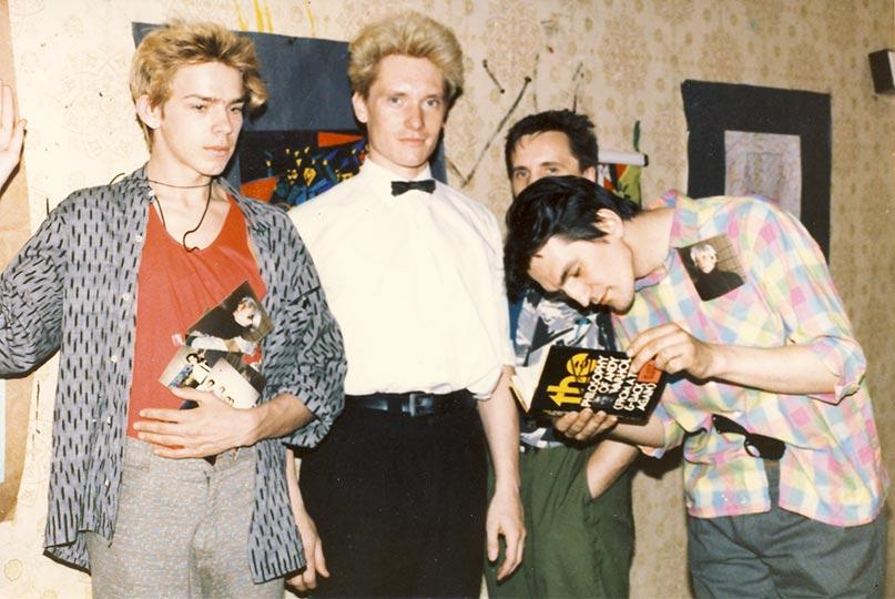 Sergei 'Afrika' Bugaev, Georgy Gurjanov, Oleg Kolomiychuk and Timur Novikov holding a book gifted by Andy Warhol at the ASSA gallery