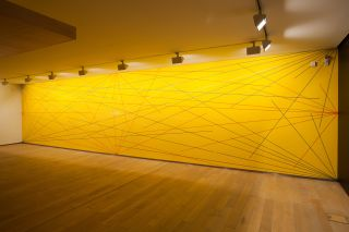 Wall Drawing 280: A six-inch (15cm) grid covering a yellow wall. Blue lines from the four corners, red lines from the midpoints of the four sides, white lines from the centre to points on the grid.