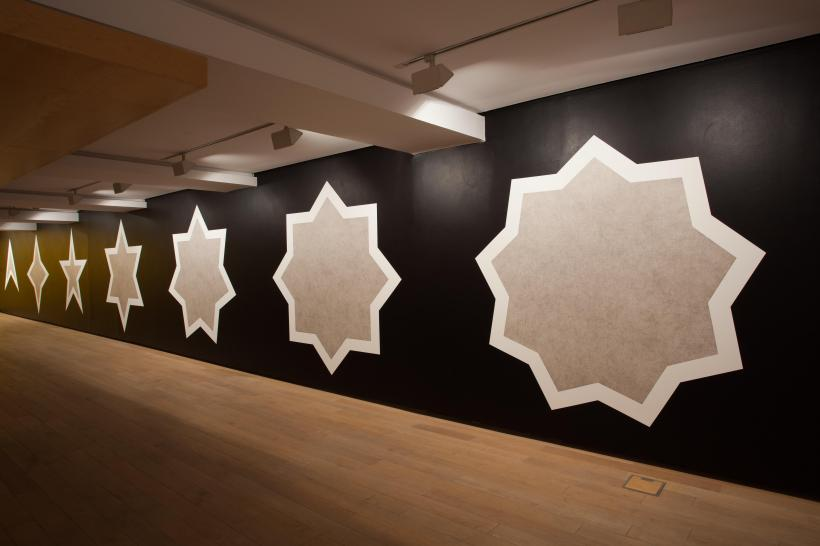 Wall Drawing 386: Stars with three-, four-, five-, six-, seven-, eight-, and nine-points, drawn with a light tone India ink wash inside, an India ink wash outside, separated by a six-inch (15 cm) white band (A-G)