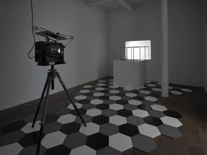 Charles Avery, Installation view of Untitled (Dihedra), 2010-12 16mm projection, steel cage, steel tiles, plinth, projector, looper, tripod Dimensions vary