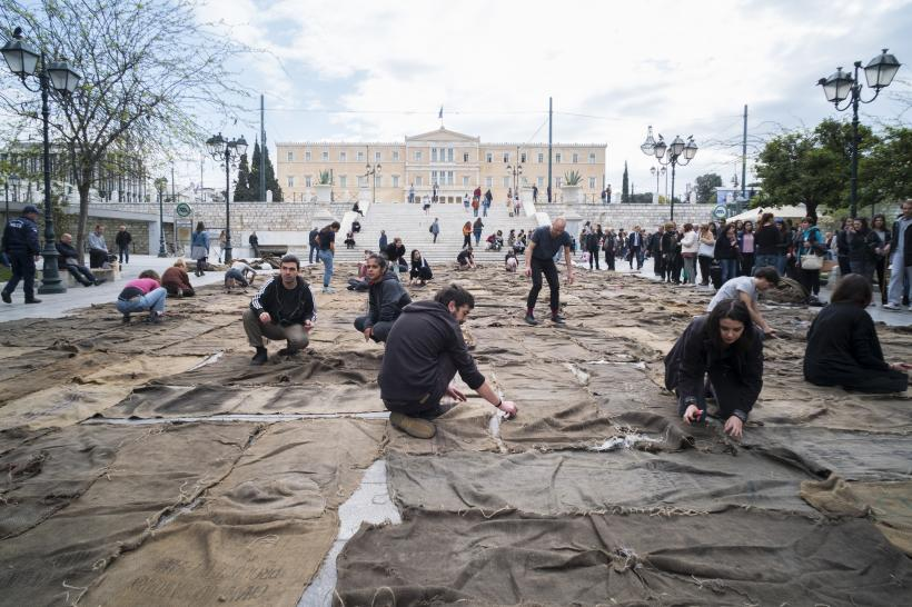 Ibrahim Mahama, Check Point Prosfygika. 1934–2034. 2016–2017, 2017, performance with charcoal sacks on Syntagma Square, Athens, documenta 14