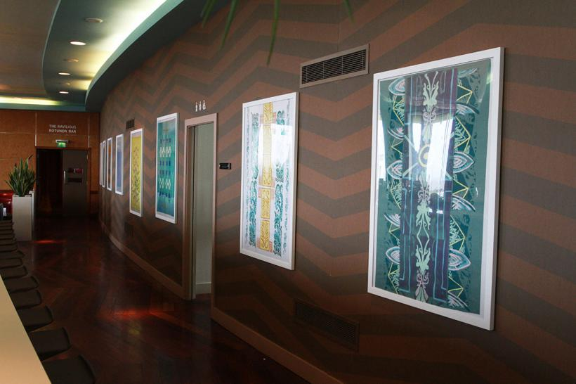 Gallery wall of screen prints on fabric and paper in bar walkway, 2017