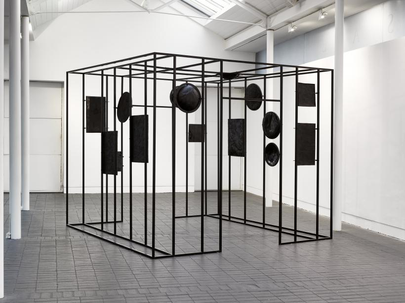 Tana West, Through a Glass Darkly, 2019. Black glazed ceramics and steel frame.